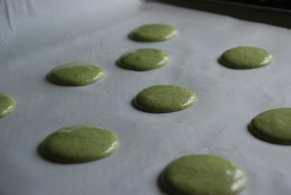 Piping matcha green tea macarons