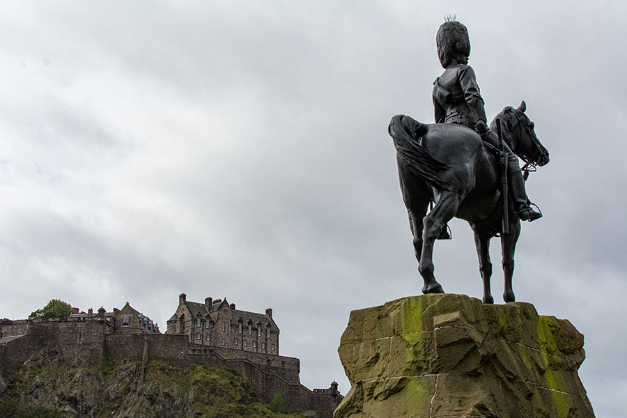 The Royal Scots Greys monument stands proudly before Edinburgh Castle in the distance.